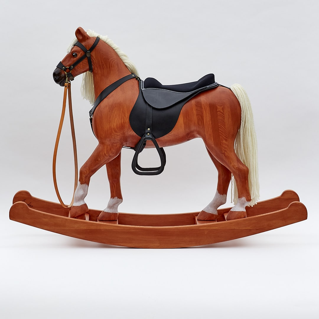 The Čenda 53 chestnut coloured wooden rocking horse comes equipped with a leather harness and a saddle