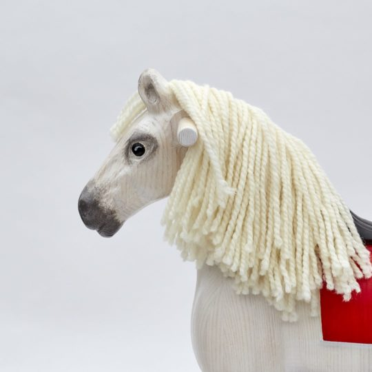 Detail on head of wooden rocking horse, white colors