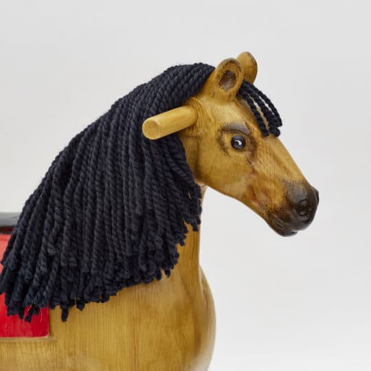 Detail on head of wooden rocking horse, tan colors