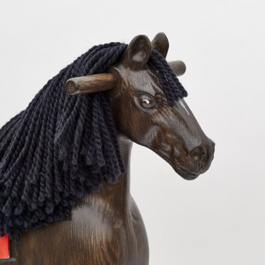 Detail on head of wooden rocking horse, black colors