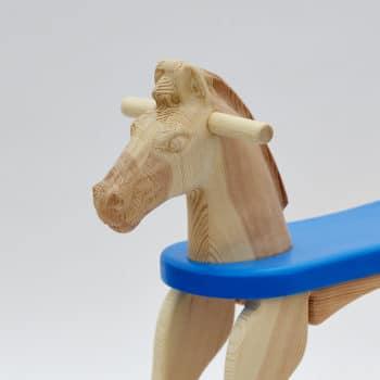 Detail hlavy dřevěného houpacího koníka v přírodní povrchové úpravě a s modrým sedátkem